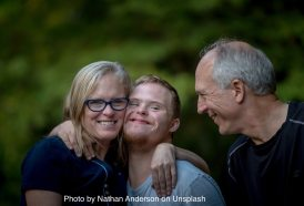 Man, woman and young man with a learning disability looking happy