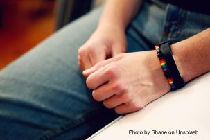 Image of person with rainbow friendship bracelet clasping their hands