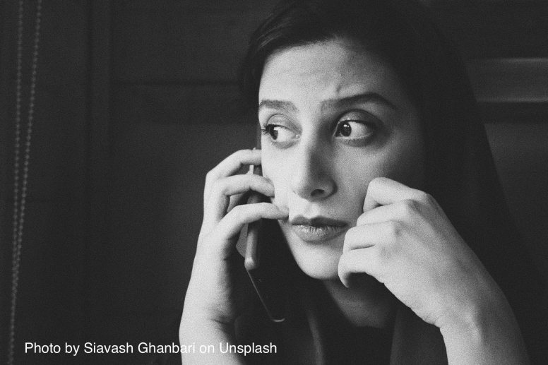 Image of person on phone, looking thoughtful